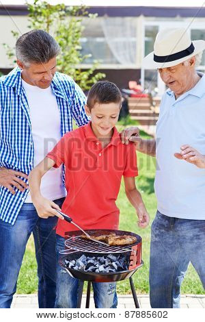 Modern senior man, young man and boy cooking barbecue