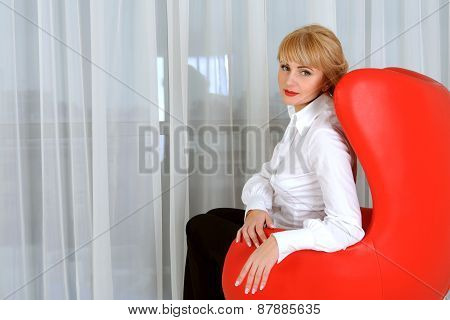 Business Woman Sitting In A Red Chair