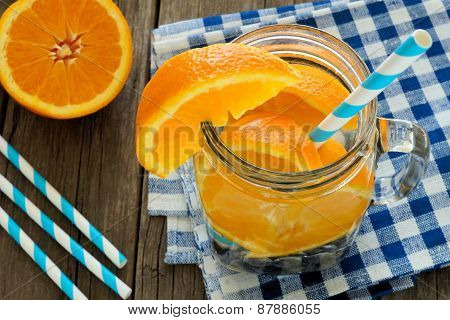 Detox water with oranges and blueberries above view in jar