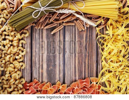 Different types of pasta on wooden background