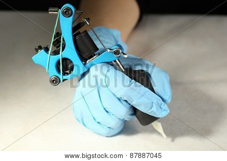 Tattoo machine in hand of Tattoo artist, close-up. on light background
