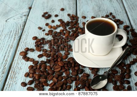 Cup of coffee with beans on color rustic wooden background