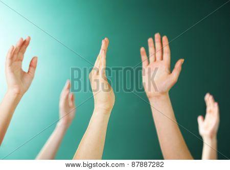 Raised hands on blackboard background in class