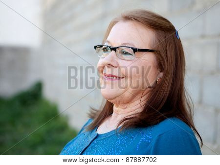 Elderly woman in her 68 years smiling outdoors