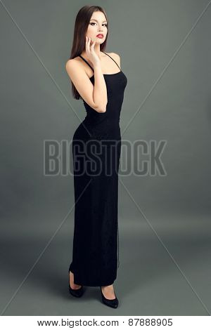 Beautiful young woman in black dress on dark gray background