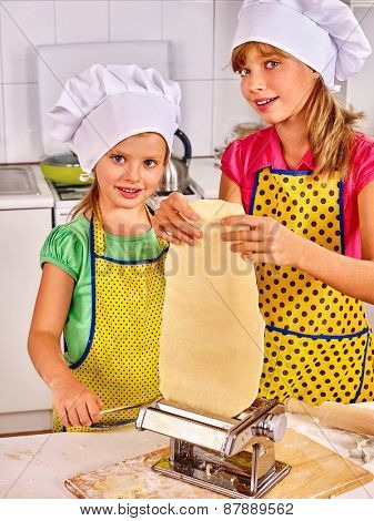 Mother and child making homemade pasta at kitchen.