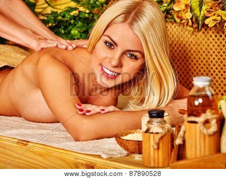 Blond woman getting massage in tropical spa.