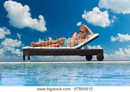Young woman in bikini  by the swimming pool