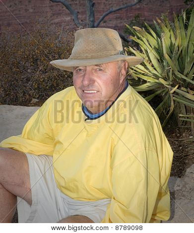 Senior Male Sitting Outdoors In Nature