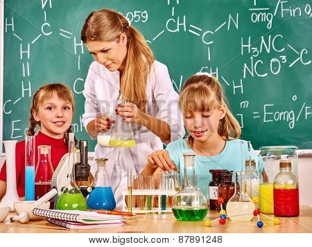 Teacher with children holding flask in chemistry class.