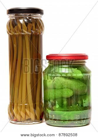 Preserved food in glass jars, isolated white background. Various marinaded . Wild garlic, cucumbers