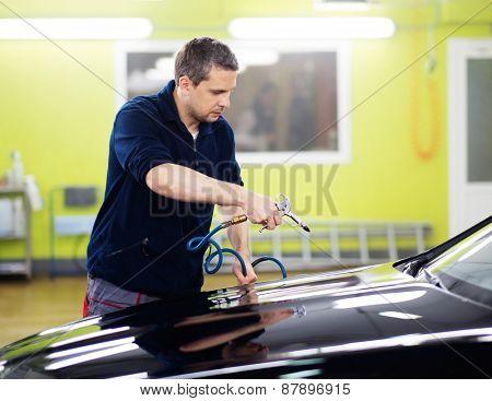 Man worker drying car on a car wash