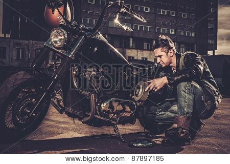 Biker repairing his custom motorcycle bobber on a road
