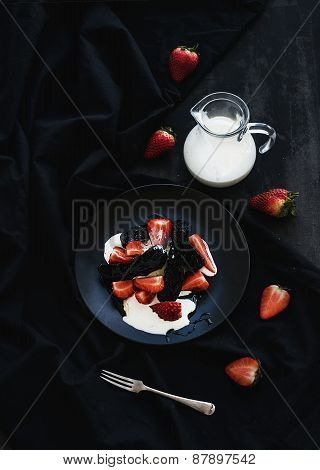 Black biscotti and strawberry dessert with sweet cream over black backdrop