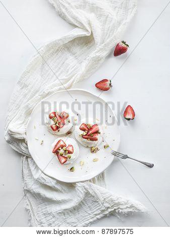 Small strawberry and pistachio pavlova meringue cakes with mascarpone cream, fresh mint over white b