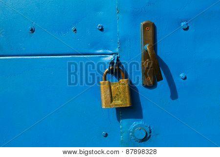 Blue Metal Door With A Padlock.
