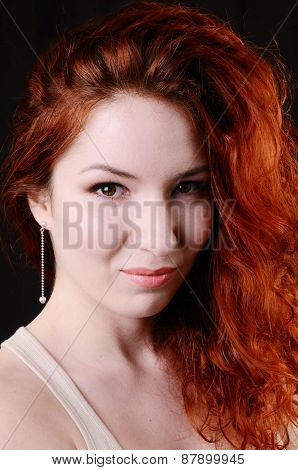 Beautiful young redhead woman with perfect daytime makeup and long silver earrings smiling playfully