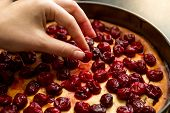picture of cherry pie  - Closeup photo of woman decorating pie with cherries - JPG