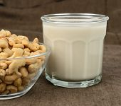 pic of milk glass  - A glass of cashew milk with a bowl of cashews on a brown tablecloth - JPG