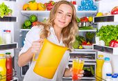 image of refrigerator  - Happy woman standing near open refrigerator full of fresh fruits and vegetables and pouring juice in glass - JPG