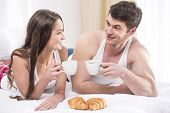 pic of bed breakfast  - Smiling young couple having breakfast in bed - JPG