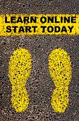 stock photo of start over  - Conceptual image with yellow paint footsteps on the road in front of horizontal line over asphalt stone background - JPG