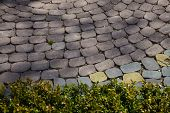 foto of paving  - Figured colored paving slabsFigured paving slabs on the ground near the green lawn - JPG