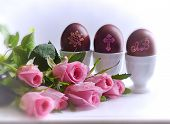 picture of three life  - Spring still life in Easter with pink roses and three colored eggs in the stands - JPG
