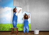 stock photo of overhauling  - Little twins doing repair at home hanging wallpaper - JPG