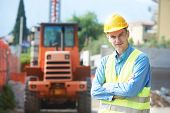 image of construction  - construction worker in safety protective work wear at construction site in front of loader machinery - JPG