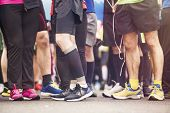stock photo of race track  - Detail of the legs of runners at the start of a marathon race - JPG