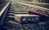 foto of old suitcase  - Two old fashioned forgotten a suitcases lie on railroad tracks - JPG
