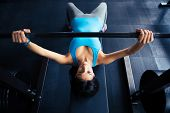 foto of work bench  - Young fit woman working out with barbell on bench in the gym - JPG