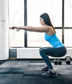 stock photo of side-views  - Side view portrait of a young woman doing squats at fitness gym - JPG