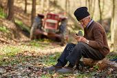 pic of man chainsaw  - Old farmer doing maintenance work to his chainsaw - JPG