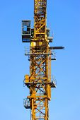 picture of heavy equipment operator  - Construction yellow crane tower with operator cabin isolated on blue sky background - JPG
