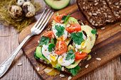 picture of avocado  - Bruschetta with tomato, avocado and quail egg on a wooden table