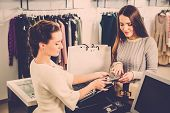 picture of showrooms  - Happy woman customer paying with credit card in fashion showroom - JPG