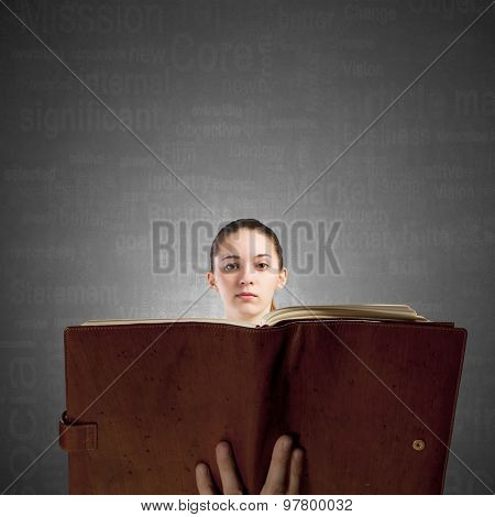 Young woman with opened book in hands