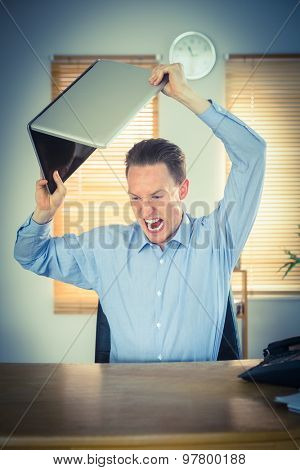Furious businessman about to smash his laptop in the office