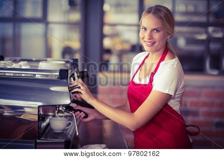 Portrait of a pretty barista preparing coffee at the coffee shop