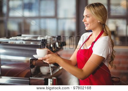 Pretty barista handing a cup of coffee at the coffee shop