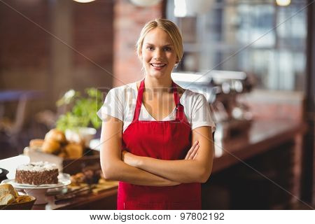 Portrait of a pretty barista with arms crossed at the coffee shop