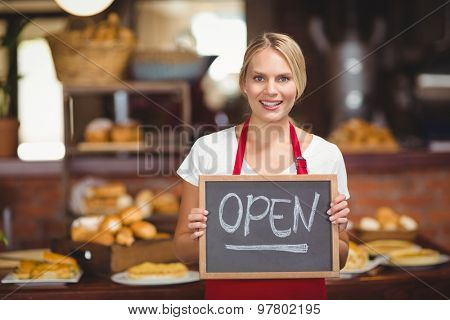 Portrait of a waitress with a chalkboard open sign at the coffee shop