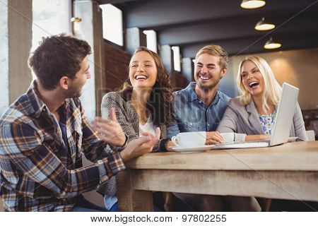 Smiling friends drinking coffee and laughing at coffee shop