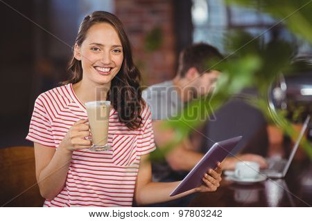 Portrait of smiling young woman enjoying latte and using tablet computer at coffee shop
