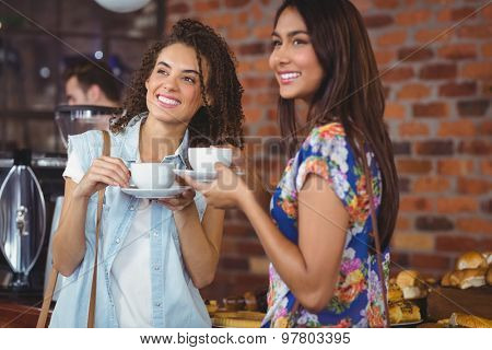 Smiling pretty customers with coffee cups at coffee shop