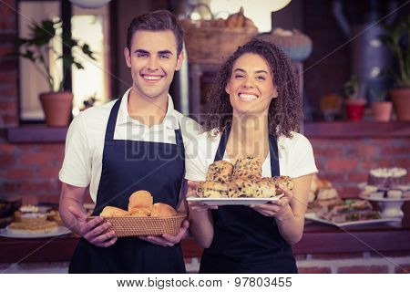 Portrait of smiling waiter and waitress holding bread bun at coffee shop