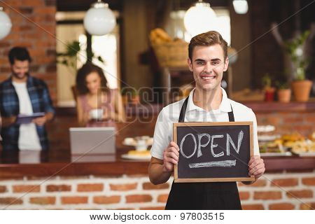 Portrait of smiling barista holding chalkboard with open sign at coffee shop