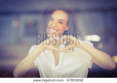 Portrait of a woman making heart shape at the coffee shop